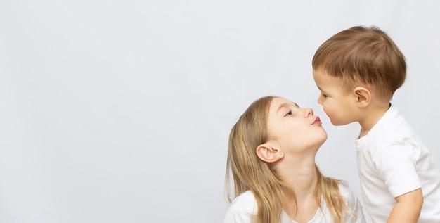 Piękny brat i siostra całują się z banerem przestrzeni kopii