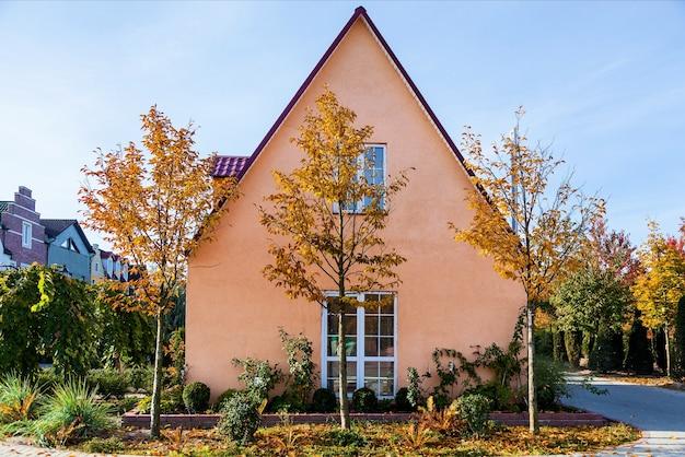 Piękny brązowy piętrowy dom obok drzew z żółtymi liśćmi na tle błękitnego nieba.