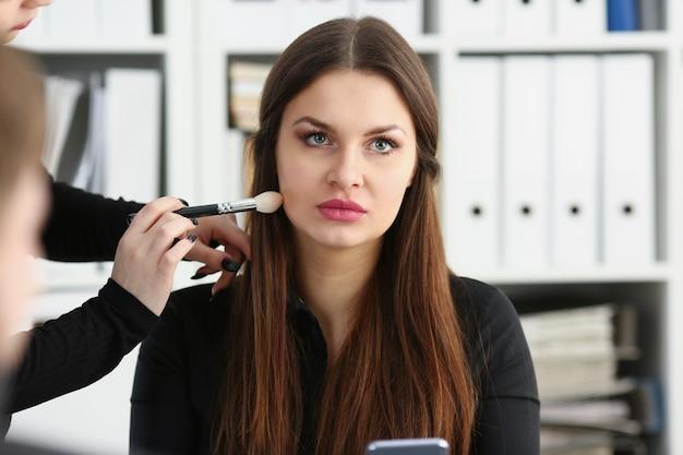 Piękny brunetka bizneswomanu chwyt w ręka telefonie przy miejsce pracy portretem dostaje dostaje makeup narządzanie dla tv powietrza. negocjuj spotkanie praca zajęty styl życia urządzenia sklep koncepcja