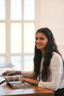Piękny brunetka uczeń podczas gdy trenujący jej lekcję i siedzący przy drewnianym pracującym biurkiem nad wygodnym siedzącym pokojem