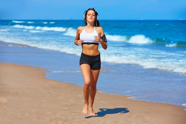 Piękny brunetki dziewczyny bieg w lato plaży