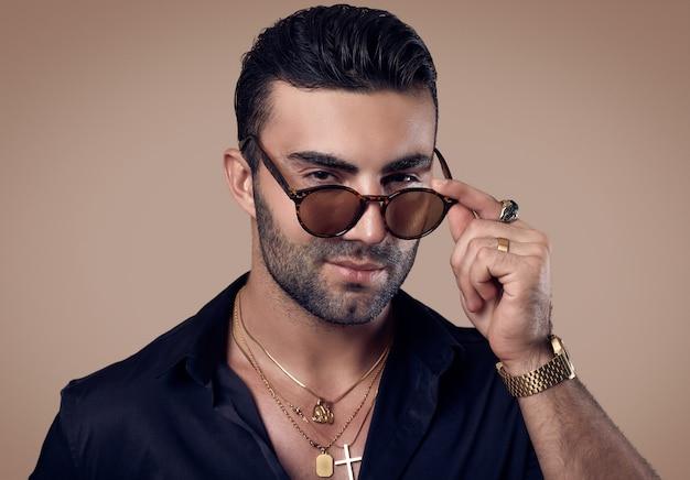 Piękny brutalny opalony hipster mężczyzna w czarnej koszuli i okularach
