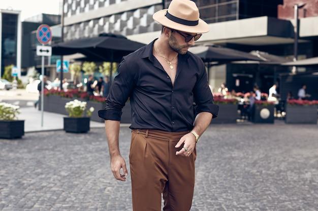 Piękny brutalny opalony muskularny mężczyzna hipster pozowanie na ulicach