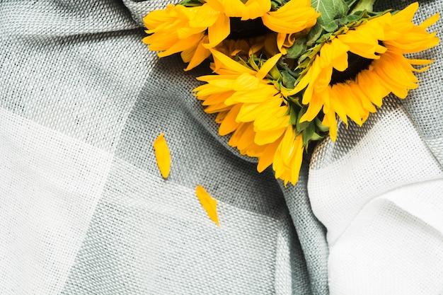 Piękny bukiet autentycznych żółtych słoneczników na szarym, kratowym widoku zbliżenia