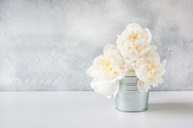 Piękny bukiet białych kwiatów piwonii w wazonie.