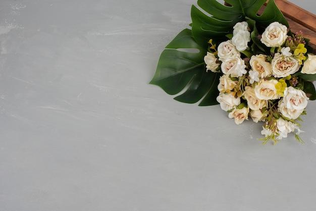 Piękny bukiet białych róż na szarej powierzchni.