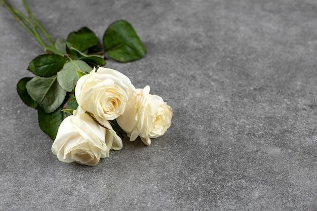 Piękny bukiet białych róż ułożonych na marmurze.