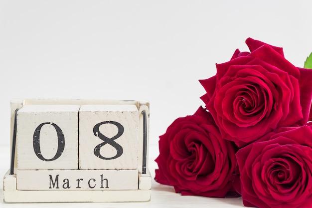 Piękny bukiet czerwonych róż i drewniany sześcian kalendarz na drewnianym tle. koncepcja gratulacji 8 marca lub dnia woomana.