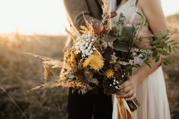 Piękny bukiet dzikich kwiatów w rękach panny młodej