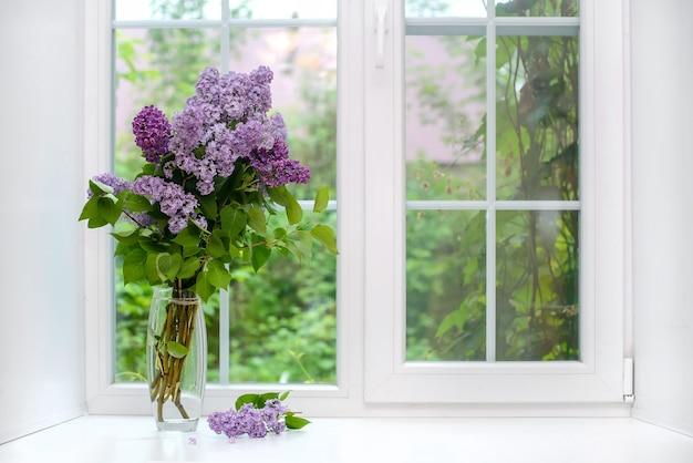 Piękny bukiet fioletowego bzu w szklanym wazonie na białym parapecie, kopia przestrzeń