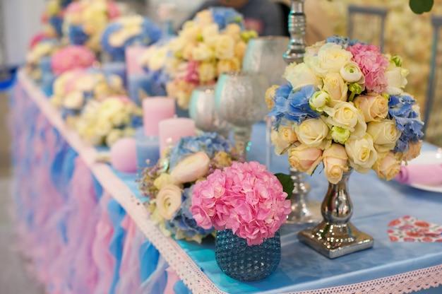 Piękny bukiet kwiatów przy stole weselnym w wystroju restauracji.