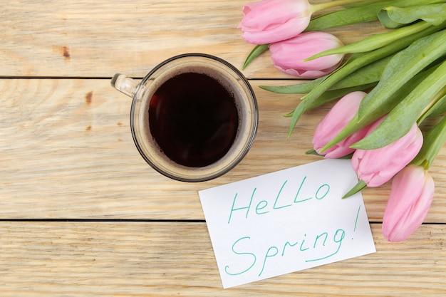 Piękny bukiet kwiatów różowych tulipanów, filiżanka kawy i napis witaj wiosnę na papierze na naturalnej drewnianej powierzchni