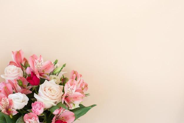 Piękny bukiet kwiatów róży i alstremerii na jasnym tle. koncepcja karty z pozdrowieniami. stylowa kompozycja florystyczna. skopiuj miejsce