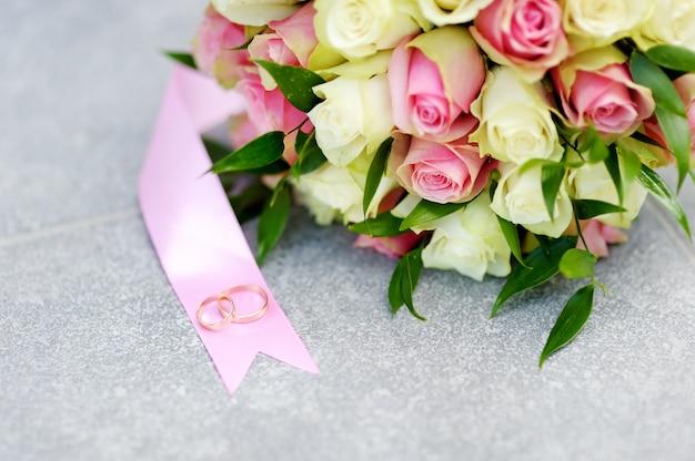 Piękny bukiet kwiatów ślubnych z żółtymi i różowymi różami i dwoma złotymi obrączkami