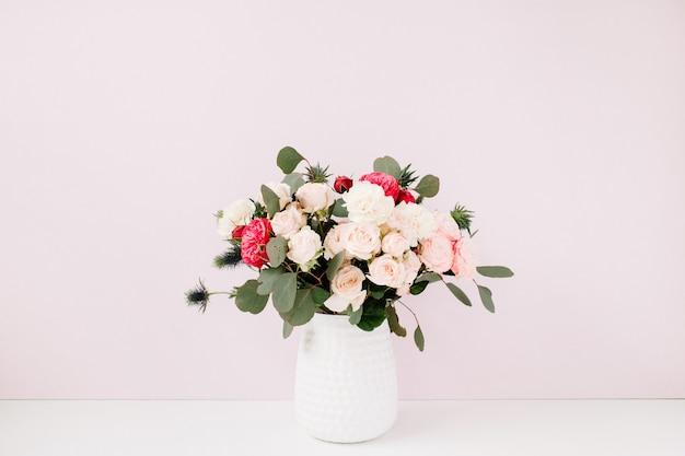 Piękny bukiet kwiatów w doniczce w pobliżu blado pastelowej różowej ściany