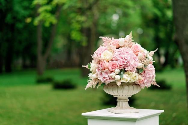 Piękny bukiet kwiatów w kamiennym wazonie stoi na kolumnie na zieleni. wystrój na ślub.