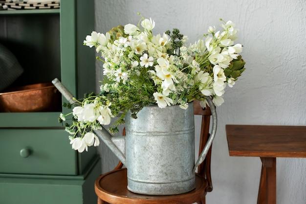 Piękny bukiet kwiatów w konewce na krześle w zabytkowej kuchni