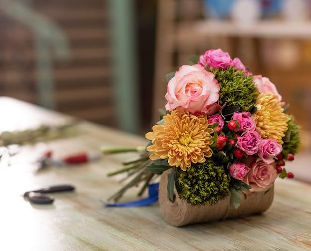 Piękny bukiet kwiatów w tabeli z wyposażeniem kwiaciarni bukiet