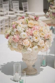 Piękny bukiet róż w wazonie na tle łuku ślubnego. piękny zestaw na ceremonię ślubną.