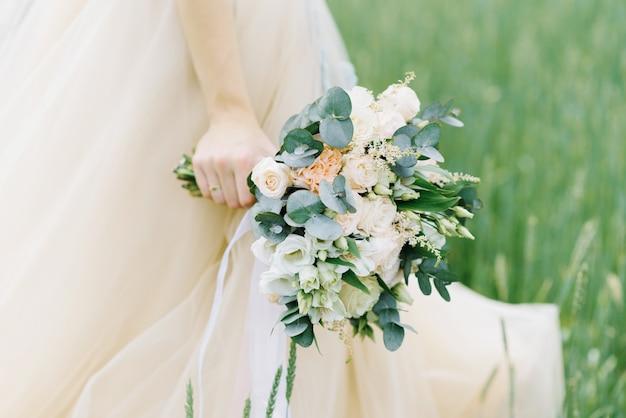 Piękny bukiet rozczochrany w rękach panny młodej w beżowej sukience