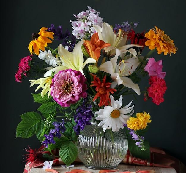Piękny bukiet różnych kwiatów ogrodowych i gałąź malin w szklanym dzbanku.