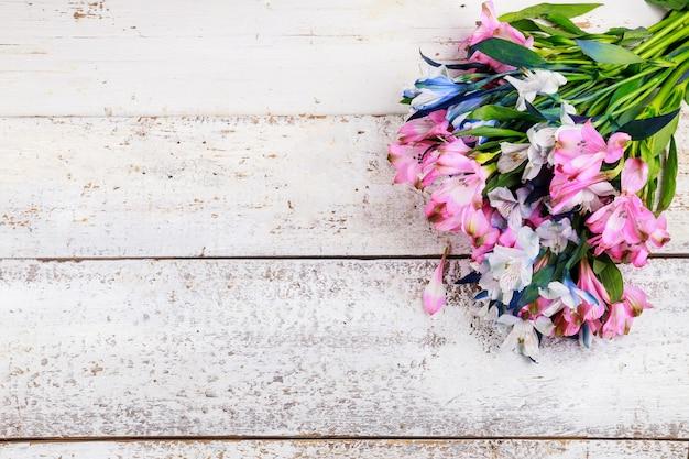 Piękny bukiet różowo-niebieskich alstremerii na białej drewnianej powierzchni.