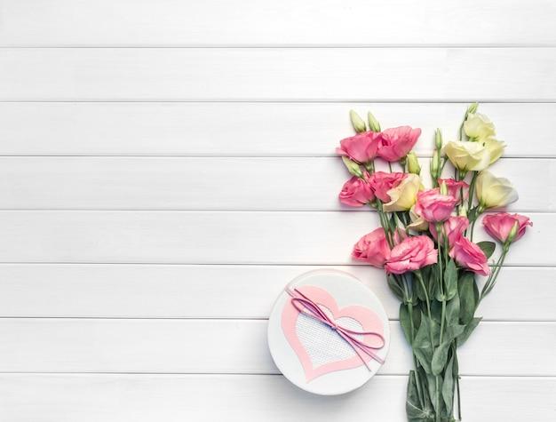 Piękny bukiet różowych, fioletowych, żółtych kwiatów eustomy i ręcznie robione pudełko na białym tle drewnianych. skopiuj miejsce, widok z góry