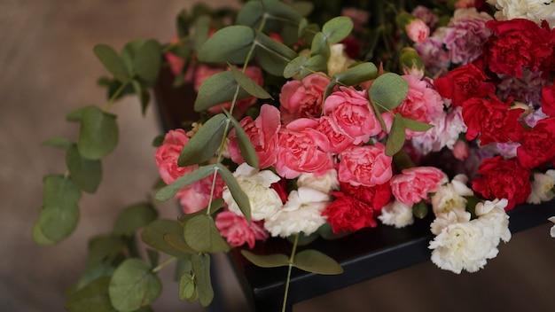 Piękny bukiet różowych i białych goździków. bukiet z zielonymi gałązkami leży na ciemnym tle z teksturą