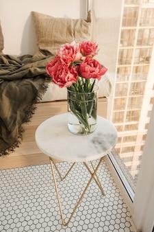Piękny bukiet różowych piwonii w szklanym wazonie na marmurowym stole.
