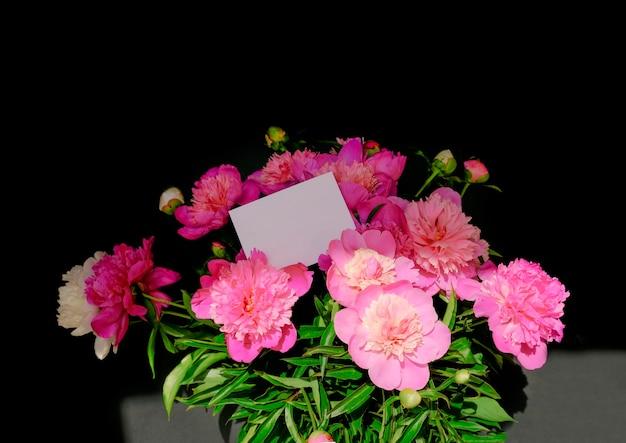 Piękny bukiet różowych piwonii z pustą białą kartką do umieszczenia wiadomości. bukiet umieszczony jest na ciemnym tle