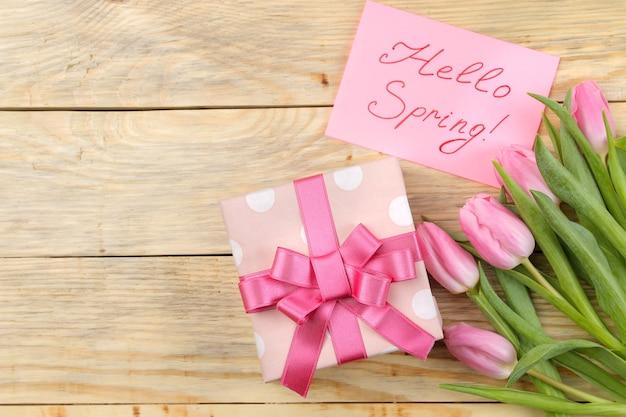 Piękny bukiet różowych tulipanów, pudełko i napis witaj wiosnę na papierze na naturalnej powierzchni drewnianej