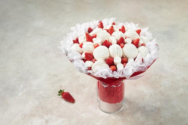 Piękny bukiet składający się z pianek, dojrzałych truskawek i czerwonych słodyczy w wazonie na marmurze