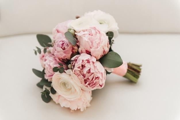 Piękny bukiet ślubny dla panny młodej z różowymi piwoniami i białymi różami piwonii