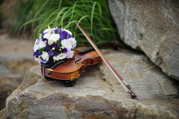 Piękny bukiet ślubny i skrzypce na skale