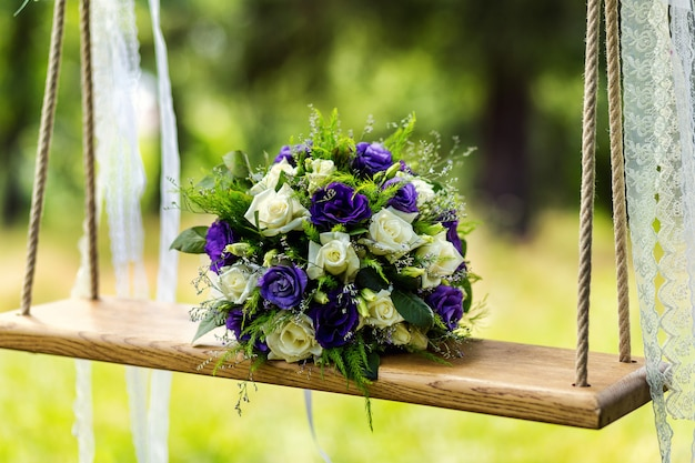 Piękny bukiet ślubny leży na huśtawce