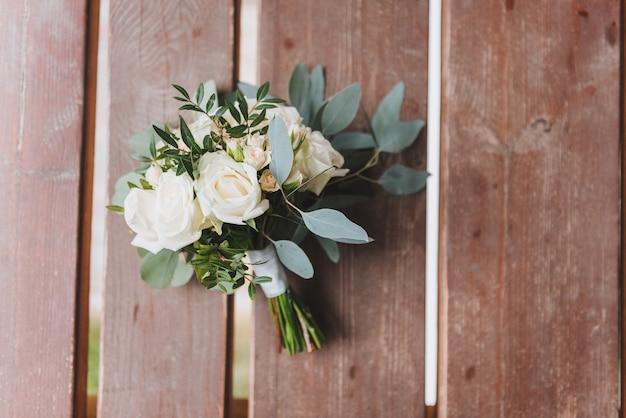 Piękny bukiet ślubny na białym tle na drewnianej ławce