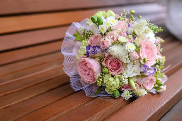 Piękny bukiet ślubny na zbliżenie brązowej drewnianej ławce