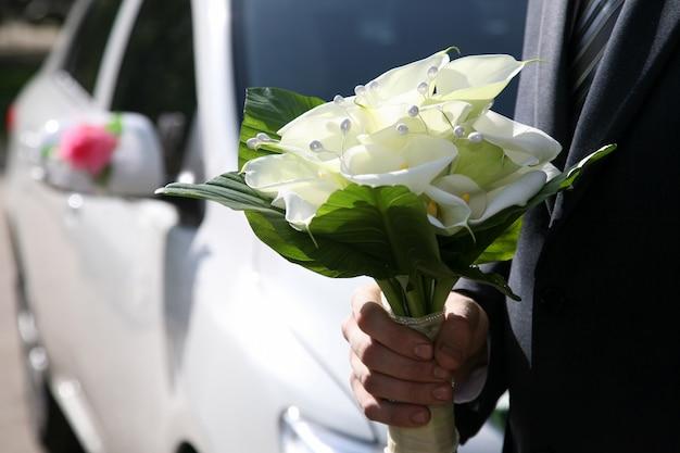 Piękny bukiet ślubny w dłoni pana młodego