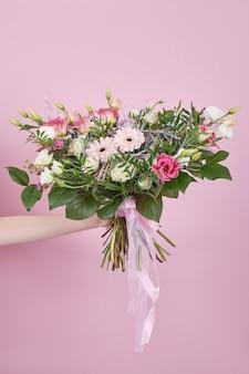Piękny bukiet ślubny w ręku na różowym tle. delikatne kwiaty