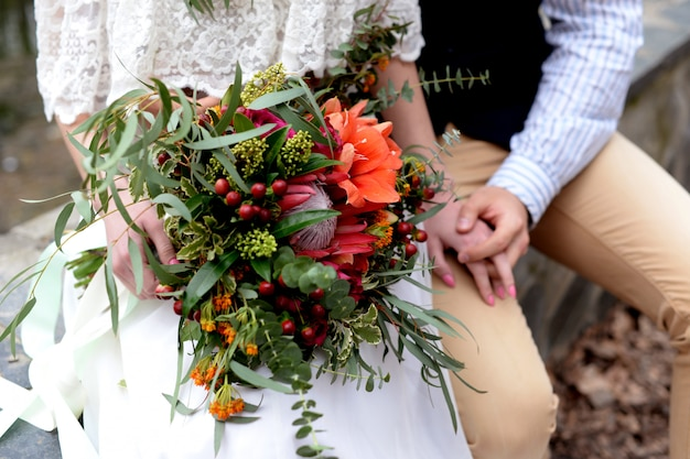 Piękny bukiet ślubny w stylu rustykalnym w rękach nowożeńców
