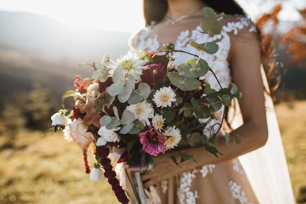 Piękny bukiet ślubny wykonany z eukaliptusa i kolorowych kwiatów w rękach dziewczynki na zewnątrz w słoneczny dzień