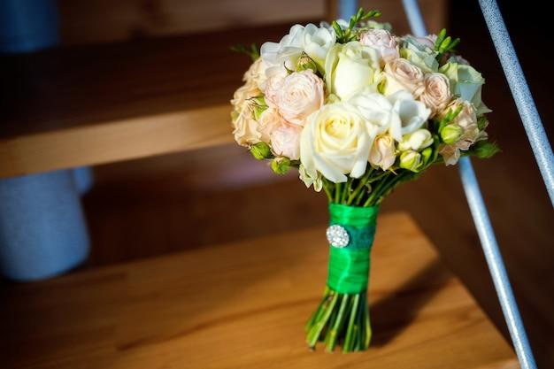 Piękny bukiet ślubny z białymi i różowymi różami dla panny młodej.