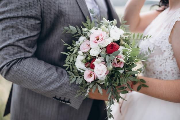 Piękny bukiet ślubny z czerwonymi, różowymi i białymi kwiatami, różami i eukaliptusem, piwoniami, liliami calla