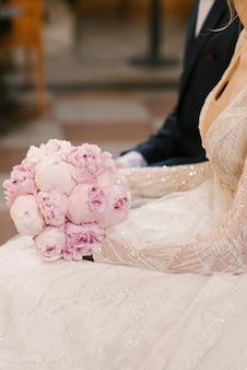 Piękny bukiet ślubny z różowych piwonii w rękach panny młodej obok pana młodego
