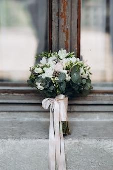 Piękny bukiet ślubny z satynowym wzorem stoi na komórce okna