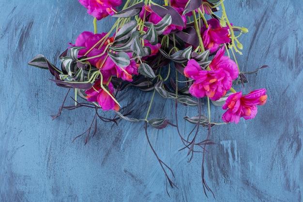 Piękny bukiet świeżych fioletowych kwiatów na niebiesko.