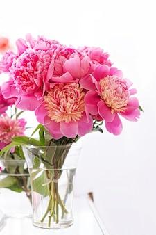 Piękny bukiet świeżych kwiatów piwonii w przezroczystym szklanym wazonie na białym tle