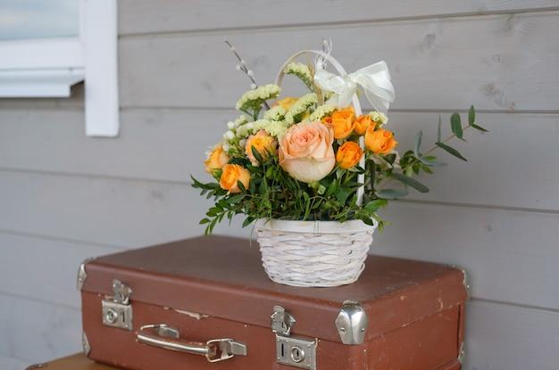 Piękny bukiet świeżych kwiatów w koszu na zabytkowej walizce na szarej ścianie