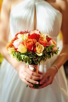 Piękny bukiet świeżych kwiatów w rękach panny młodej w białej sukni. zbliżenie kwiatów ślubu