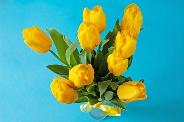 Piękny bukiet tulipanów na niebieskim tle